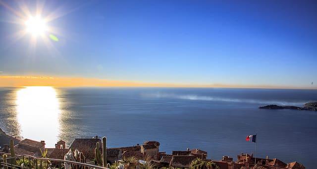 Photographie de la mer avec un grand soleil à l'horizon.